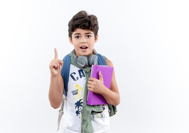 Pod wrażeniem mały uczeń noszenia plecaka i słuchawek, trzymając książkę i wskazuje na górę na białym tle na białym tle z miejsca kopiowania