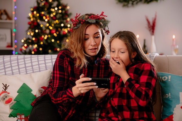 Pod wrażeniem matka i córka oglądają coś na telefonie, siedząc na kanapie i ciesząc się świątecznymi chwilami w domu