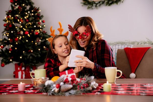 Pod wrażeniem matka w okularach renifera patrząc na notebooka z córką siedzącą przy stole, ciesząc się świątecznym w domu