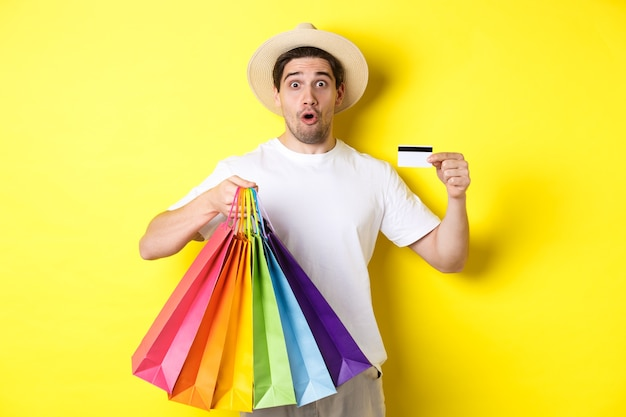Pod wrażeniem mężczyzna pokazuje torby na zakupy z produktami i kartą kredytową, stojąc na żółtym tle.