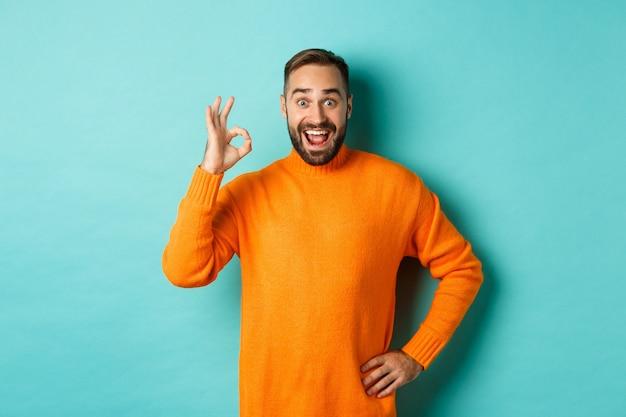 Pod wrażeniem mężczyzna polecający promocję, pokazujący znak dobra i uśmiechnięty zdumiony, aprobuje i zgadza się, stojąc nad jasną turkusową ścianą.