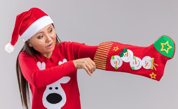Pod wrażeniem młoda azjatycka dziewczyna ubrana w świąteczny kapelusz ze swetrem, wkładając rękę w świąteczne skarpety na białym tle na białej ścianie