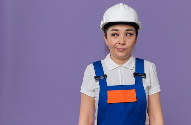 Pod wrażeniem młoda azjatycka kobieta budowlana z białym hełmem ochronnym patrząca na bok