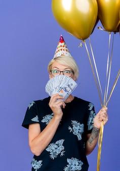 Pod wrażeniem młoda blond impreza w okularach i czapce urodzinowej, trzymając balony i pieniądze, patrząc na kamery zza pieniędzy na białym tle na fioletowym tle
