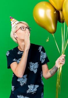 Pod wrażeniem młoda blond impreza w okularach i czapce urodzinowej, trzymając i patrząc na balony szeptem na białym tle na zielonym tle