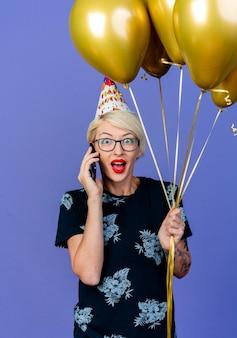 Pod wrażeniem młoda blond kobieta w okularach i czapce urodzinowej, trzymając balony, rozmawiając przez telefon, patrząc na przód na białym tle na fioletowej ścianie