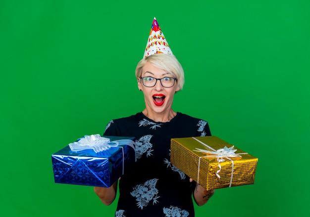 Pod wrażeniem młoda blond kobieta w okularach i czapce urodzinowej, trzymając pudełka na prezent, patrząc z przodu na białym tle na zielonej ścianie