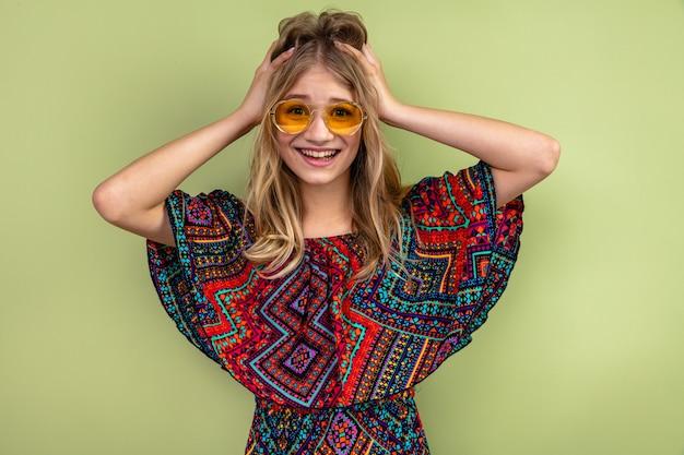 Pod wrażeniem młoda blond słowiańska dziewczyna w okularach przeciwsłonecznych, kładąca ręce na głowie i
