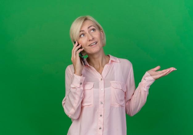 Pod wrażeniem młoda blond słowiańska kobieta, patrząc w górę, rozmawiając przez telefon i pokazując pustą rękę na białym tle na zielonym tle z miejsca na kopię