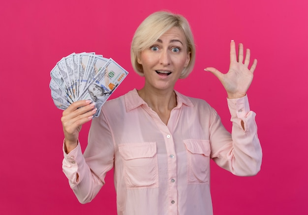 Pod wrażeniem młoda blond słowiańska kobieta trzyma pieniądze i gestykuluje cześć ręką odizolowaną na różowym tle
