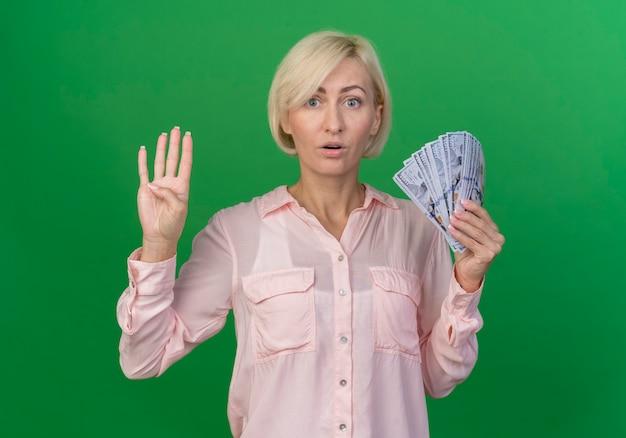 Pod wrażeniem młoda blond słowiańska kobieta trzyma pieniądze i pokazuje cztery ręką na białym tle na zielonym tle