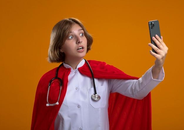 Pod wrażeniem młoda blond superbohaterka w czerwonej pelerynie ubrana w mundur lekarza i stetoskop, biorąc selfie na pomarańczowej ścianie