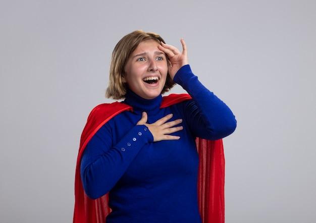 Pod wrażeniem młoda blond superwoman w czerwonej pelerynie, patrząc prosto, trzymając rękę na klatce piersiowej, dotykając głowy na białym tle na białej ścianie