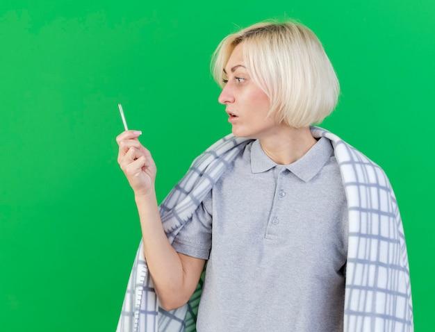 Pod wrażeniem młoda blondynka chora słowiańska kobieta, owinięta w kratę, trzymając i patrząc na termometr