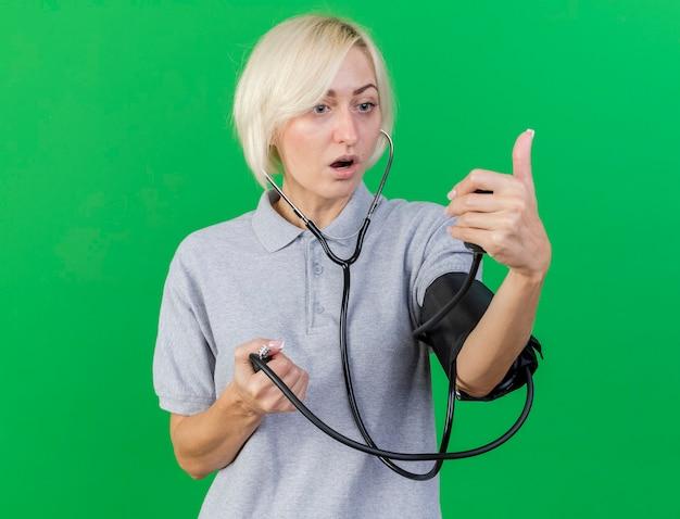 Pod wrażeniem młoda blondynka chora słowiańska kobieta szuka i mierzy ciśnienie