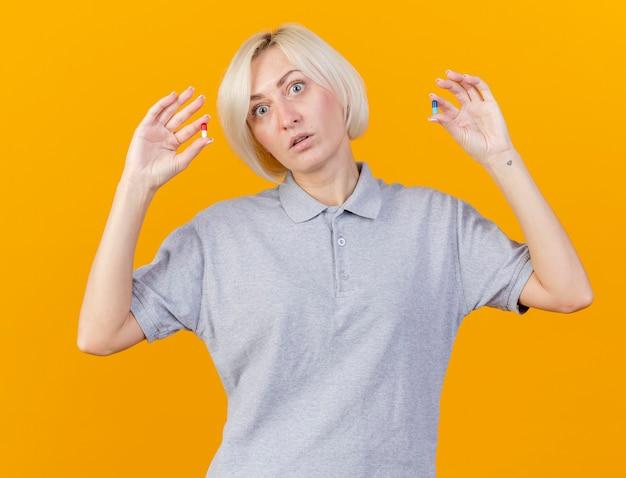 Pod wrażeniem młoda blondynka chora słowiańska kobieta trzyma pigułki medyczne odizolowane na pomarańczowo