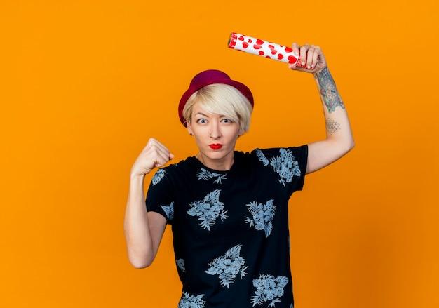 Pod wrażeniem młoda blondynka imprezowa dziewczyna w kapeluszu imprezowym podnosząca konfetti armata zaciskająca pięść patrząc na kamerę odizolowaną na tle z miejsca na kopię
