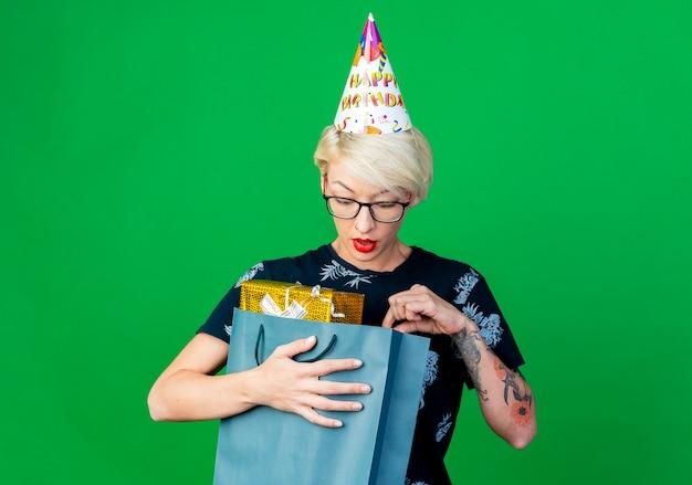 Pod wrażeniem młoda blondynka imprezowa w okularach i czapce urodzinowej, trzymająca i zaglądająca do papierowej torby z pudełkami na prezenty odizolowane na zielonym tle z miejscem na kopię