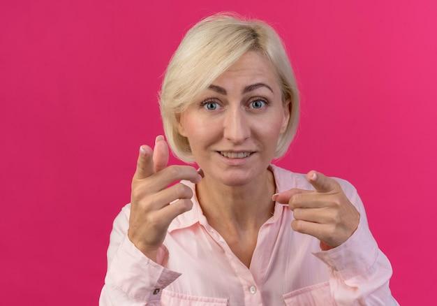 Pod wrażeniem młoda blondynka słowiańska kobieta patrząc i wskazując na aparat na białym tle na różowym tle