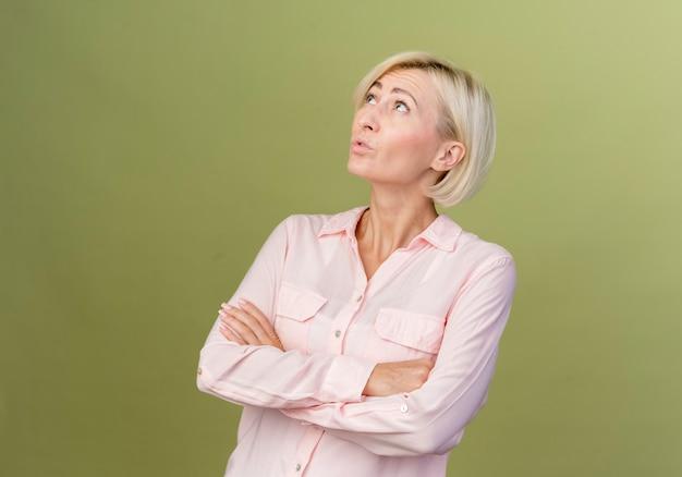 Pod wrażeniem młoda blondynka słowiańska skrzyżowane ręce na białym tle na oliwkowej zieleni