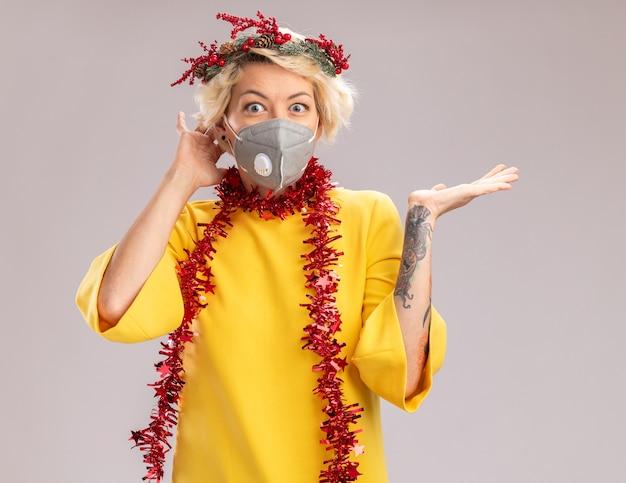 Pod wrażeniem młoda blondynka ubrana w świąteczny wieniec na głowę i girlandę z blichtru wokół szyi z maską ochronną trzymającą rękę za głową patrzącą pokazując pustą rękę odizolowaną na białej ścianie