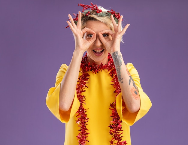 Pod wrażeniem młoda blondynka ubrana w świąteczny wieniec na głowę i świecącą girlandę na szyi, patrząc na aparat, robi gest spojrzenia, używając rąk jako lornetki na fioletowym tle