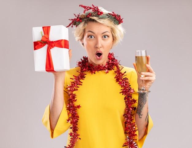 Pod wrażeniem młoda blondynka ubrana w świąteczny wieniec na głowę i świecącą girlandę na szyi trzyma kieliszek szampana i pakiet prezentów patrząc na aparat na białym tle