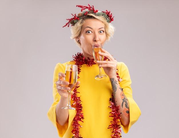 Pod wrażeniem młoda blondynka ubrana w świąteczny wieniec na głowę i świecącą girlandę na szyi trzymająca dwie szklanki szampana patrząc na kamerę pijącą jeden na białym tle