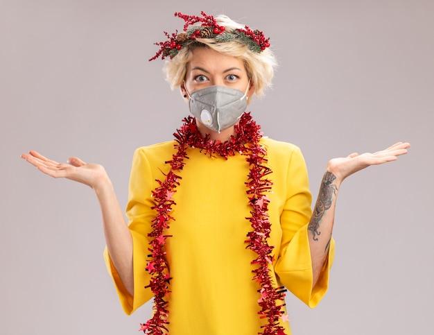 Pod wrażeniem młoda blondynka ubrana w świąteczny wieniec na głowę i świecącą girlandę na szyi z maską ochronną patrząc na kamerę pokazującą puste ręce na białym tle