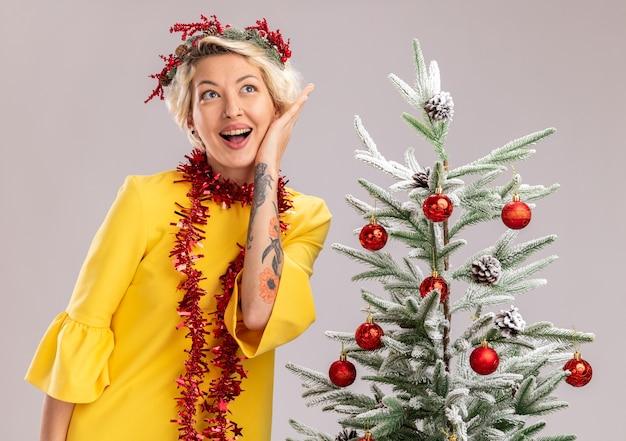 Pod wrażeniem młoda blondynka ubrana w świąteczny wieniec na głowę i świecącą girlandę wokół szyi stojąca w pobliżu udekorowanej choinki dotykająca twarzy patrząc z boku na białym tle