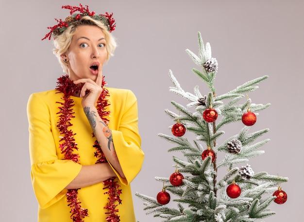 Pod wrażeniem młoda blondynka ubrana w świąteczny wieniec na głowę i świecącą girlandę wokół szyi stojąca w pobliżu udekorowanej choinki patrząc na aparat dotykając ust na białym tle