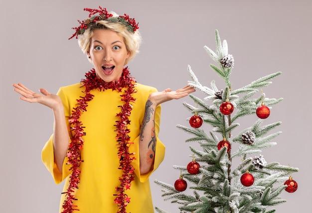 Pod wrażeniem młoda blondynka ubrana w świąteczny wieniec na głowę i świecącą girlandę wokół szyi stojąca w pobliżu udekorowanej choinki patrząc na kamerę pokazującą puste ręce na białym tle