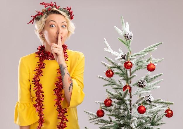 Pod wrażeniem młoda blondynka ubrana w świąteczny wieniec na głowę i świecącą girlandę wokół szyi, stojąca w pobliżu udekorowanej choinki, patrząc na kamerę, wykonująca gest ciszy na białym tle