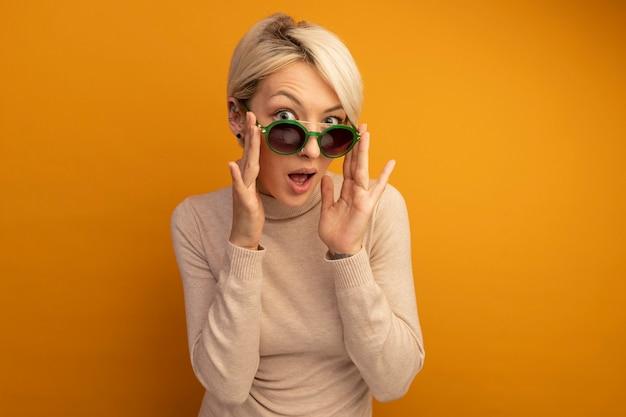 Pod wrażeniem młoda blondynka w okularach przeciwsłonecznych, kładąca na nich ręce odizolowana na pomarańczowej ścianie z miejscem na kopię