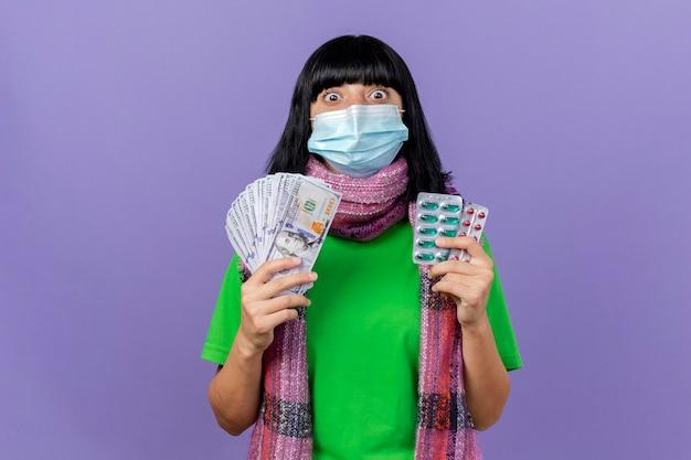 Pod wrażeniem młoda chora dziewczynka kaukaska nosząca maskę i szalik trzymająca pieniądze i paczki kapsułek patrząc na kamerę odizolowaną na fioletowym tle z przestrzenią do kopiowania