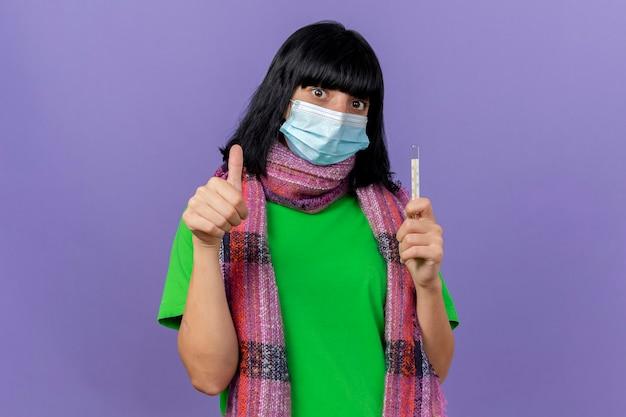 Pod wrażeniem młoda chora dziewczynka kaukaska nosząca maskę i szalik trzymająca termometr patrząc na kamerę pokazująca kciuk w górę na białym tle na fioletowym tle z miejsca na kopię