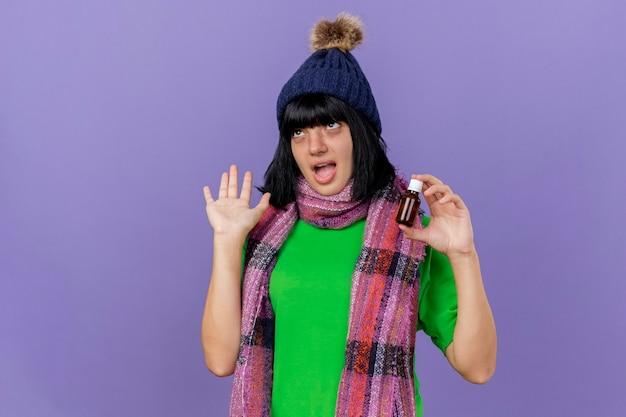 Pod wrażeniem młoda chora dziewczynka kaukaska w czapce zimowej i szaliku trzymająca lekarstwo w szkle pokazująca pustą dłoń patrząc w górę na białym tle na fioletowym tle z przestrzenią do kopiowania
