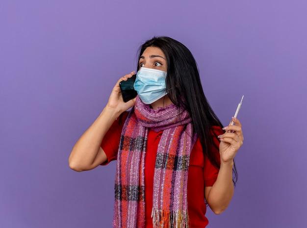 Pod wrażeniem młoda chora kobieta ma na sobie maskę i szalik trzyma termometr, rozmawia przez telefon, patrząc na bok na białym tle na fioletowej ścianie