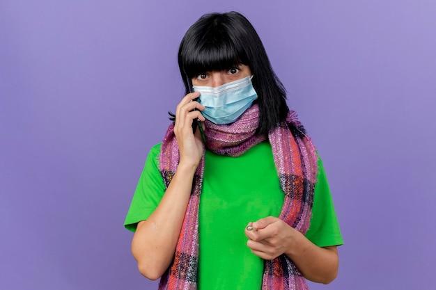 Pod wrażeniem młoda chora kobieta ubrana w maskę i szalik patrząc z przodu rozmawia przez telefon na białym tle na fioletowej ścianie z miejsca na kopię