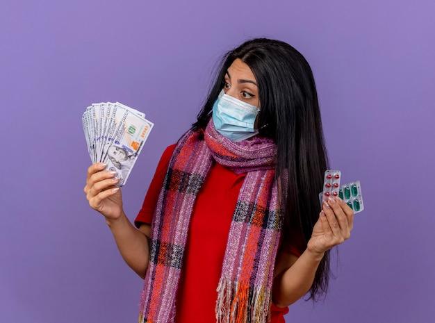 Pod wrażeniem młoda chora kobieta ubrana w maskę i szalik, trzymając pieniądze i paczkę kapsułek, patrząc na pieniądze na fioletowej ścianie