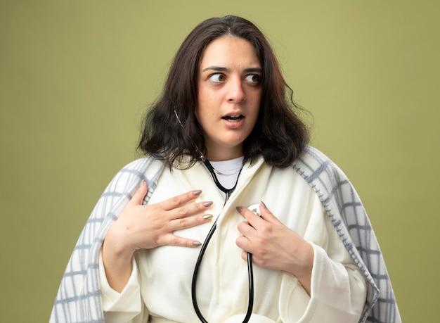 Pod wrażeniem młoda chora kobieta ubrana w szlafrok i stetoskop owinięta w kratę, słuchająca bicia jej serca, trzymająca dłoń na klatce piersiowej, patrząc z boku odizolowana na oliwkowej ścianie