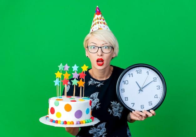 Pod wrażeniem młoda dziewczyna blonde party w okularach i czapce urodzinowej, trzymając czapkę urodzinową i zegar patrząc na kamery na białym tle na zielonym tle z miejsca na kopię