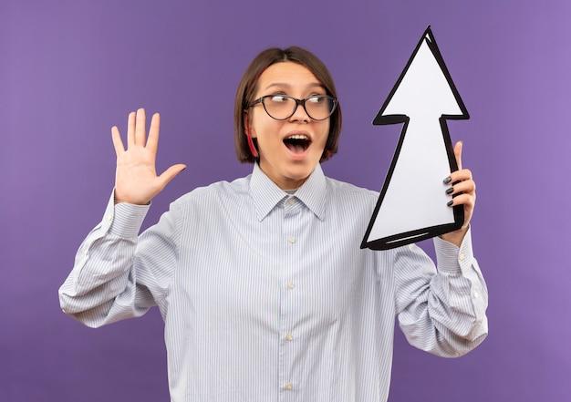 Pod wrażeniem młoda dziewczyna call center w okularach pokazując pustą rękę patrząc i trzymając znak strzałki, która jest skierowana w górę na białym tle na fioletowo