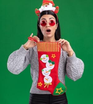 Pod wrażeniem młoda dziewczyna kaukaska ubrana w opaskę świętego mikołaja w okularach trzyma skarpety świąteczne patrząc na kamery na białym tle na zielonym tle