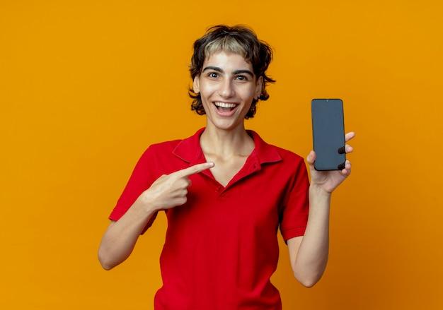 Pod wrażeniem młoda dziewczyna kaukaski z fryzurą pixie, trzymając i wskazując na telefon komórkowy na białym tle na pomarańczowym tle z miejsca na kopię