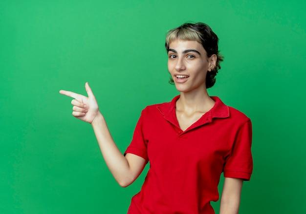 Pod wrażeniem młoda dziewczyna kaukaski z fryzurą pixie, wskazując na bok na białym tle na zielonym tle