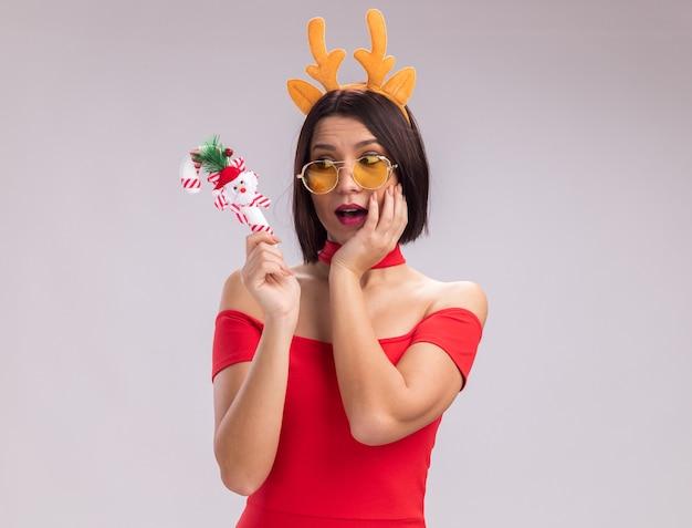 Pod wrażeniem młoda dziewczyna nosi opaskę z poroża renifera i okulary, trzymając i patrząc na świąteczną ozdobę z trzciny cukrowej, trzymając rękę na twarzy na białym tle z miejsca kopiowania