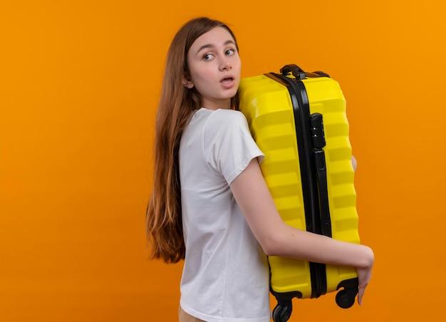 Pod wrażeniem młoda dziewczyna podróżnika, trzymając walizkę, patrząc do tyłu na odizolowanej pomarańczowej przestrzeni z kopią miejsca