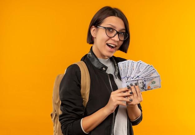Pod wrażeniem młoda dziewczyna studenta w okularach iz powrotem worek trzymając pieniądze na białym tle na pomarańczowo