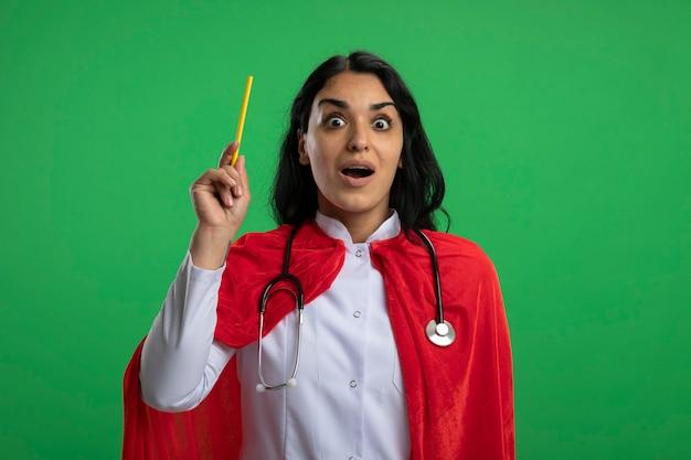 Pod wrażeniem młoda dziewczyna superbohatera ubrana w szlafrok medyczny ze stetoskopem podnosząc ołówek na białym tle na zielono